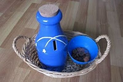 This is a ceramic bank and a bowl ofpennies for Tyler to feed through the slot. He then removes the cork to dump them out. I like that the slot is on the side so that he has to hold the penny in a different way than many of his works, which usually requ...
