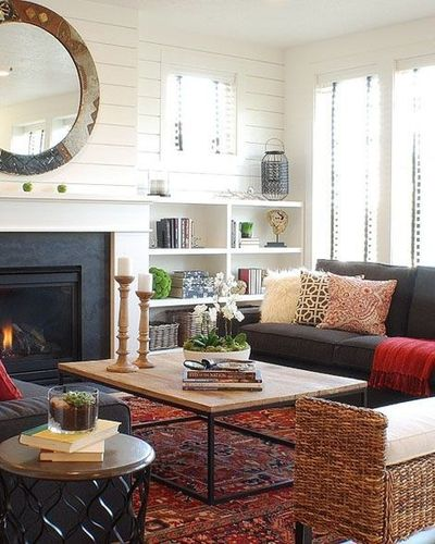 LIVING ROOM: Grey couch, interesting wood coffee table, oriental rug