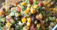 Ingredients 1- 15 oz can corn 1 can black beans 2 avocados (cubed) 2/3 cup chopped cilantro 8 green onion stalks, sliced 6 roma tomatoes Dressing: 1/4 cup olive oil 1/4 cup red wine vinegar 2 cloves minced garlic 3/4 teaspoon salt 1/8 teaspoon pep...
