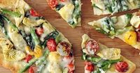 Once you've made your own pizza at home, you'll wonder why you ever called for delivery. This savory pie topped with asparagus, artichokes, and tomatoes will ha