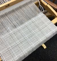 "This simple ""log cabin"" variation is easy to weave. Simply warp your loom with two alternating yarn colors of your choice. Once the warp is on the loom thread the heddle light, dark x 7, then alternate dark, light x 3. Your repeat is a total of ..."