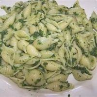 Spinach and Pasta Shells Ingredients 1 pound seashell pasta 1 (10 ounce) package frozen chopped spinach 2 tablespoons olive oil 7 cloves garlic, minced 1 teaspoon dried red pepper flakes (optional) salt to taste