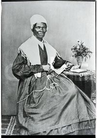 Sojourner Truth poses for a portrait while knitting at a small table. Sojourner Truth, whose legal name was Isabella Van Wagener, was born into slavery but later freed. She worked as an abolitionist, a suffragette, and an evangelist and traveled throughou...