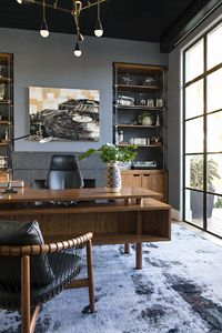 The owner's home office has custom brass and walnut built-ins that house a collection of machine parts. The walls are upholstered in grayish blue flannel, while Heidi Bonesteel designed the midcentury desk with a return that has shallow bookshelves ...