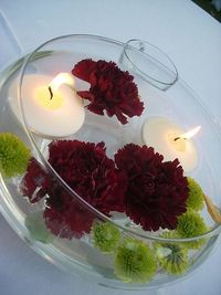 Centerpieces: floating candles with submerged flowers