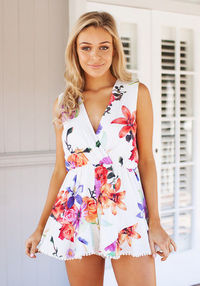 We are in love with this amazing floral playsuit featuring twisted panel at front and a plunging v neckline. Fitted waist. Bottom features crochet cuff. Zip close at back. No stretch fabric, fully lined.