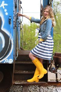 yellow rain boots, striped skirt and jean jacket spring maternity style via Laughing Latte