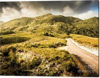 Landscape Wall Art   Scenic view of lonely gravel road leading forward towards rugged mountains covered in lush green grass. Taken Trial Harbour, Tasmania, Australia   Jorgo Photography #landscapeart #landscapeprint #wallart #acrylicart #photography #artw...