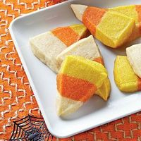 Candy Corn Cookie Bites - Colored sugar cookie dough stacked in a loaf pan, chilled, sliced and cut into triangles then baked.
