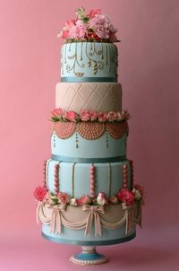 Textured tiers featuring unique details like tufting, draping, bows and pearls are accented with fresh pink rosettes.