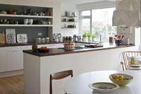 Holkham, Midwinter and Hornsea Ceramics on open shelf in kitchen of Virginia Armstrong Roddy & Ginger Retro London Home, Annie Sloan's Room Recipes, Photography by Christopher Drake | Remodelista