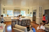 Dream White Kitchen with white cabinets, marble counter tops, blue blacksplash and open to family room