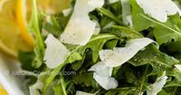 Delicious and easy arugula salad drizzled with lemon juice, olive oil, and topped with sliced Parmesan cheese. Ready in 5 minutes!