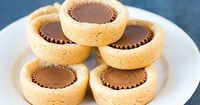 A miniature peanut butter cup is pressed into soft peanut butter cookie balls, creating a wonderful holiday cookie.