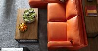 Orange leather couch in a great living room layout...