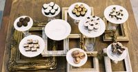 frame your desserts! The desserts are on white plates that are sitting on top of glass vases