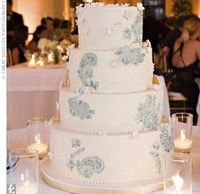 A four-tiered ivory wedding cake decorated with a light blue lace pattern, white piped dots and simple white sugar flowers