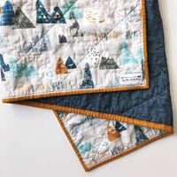This is beautiful, modern, baby quilt is ready to ship! It is a whole cloth quilt which means each side is one continuous piece of premium quilting cotton with a layer of warm cotton batting sandwiched inside. The front design features mountains and the p...