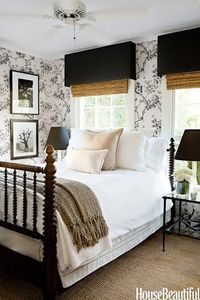 Charming bedroom with antique bed, bamboo blinds & toile wallpaper