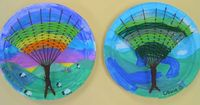 Paint a landscape scene on a Chinette paper plate. Cut approximately 9 slits at the top and two slits on the bottom for the warp strings. Weave colors on the top of the tree and dark brown at the bottom.