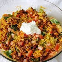 Doritos Taco Salad Recipe1 lb. ground beef 1 head iceberg lettuce, cleaned and torn into bite site pieces 1 envelope of taco seasoning 1 medium sized tomato, diced 1 bag of nacho Doritos 1 bottle French Dressing 1 ½ cup shredded cheddar cheese
