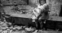 Little girl comforting her doll in the ruins of her bomb damaged home, London, 1940 | 30 Unique And Compelling Photos From Our Past