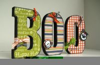 need to do this...mod podge scrapbook paper onto wood letters and use 3-D stickers to decorate.