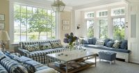 Classic and wonderful cream and faded blue sitting room in posh Oyster Harbors on Cape Cod by Catalano Design. Big gingham sofas, floral throw pillows, comfy window seat, and lovely lantern impart that sun-washed and cozy Cape Cod feel, while still being ...