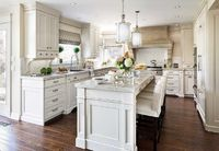 Beautiful kitchen features a pair of cylinder pendants illuminating an ivory center island topped ...