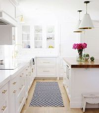 Dreamy white and gold kitchen with navy rug
