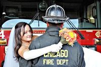 Firefighter holding bride in front of firetruck