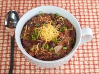 A simple chili recipe made with ground beef, tomatoes, kidney beans, tomato paste, chili powder, and topped with cheddar cheese.