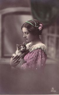 VINTAGE hand tinted photo: A young woman cuddling her kitten.
