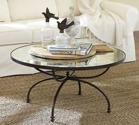 """Willow Coffee Table from Potter Barn $600 An antiqued mirror rests on an elegantly curved iron base, creating a coffee table with eye-catching presence. Its round shape lets it work well in small spaces or in rooms with L-shaped sectionals. 36"""" diame..."""