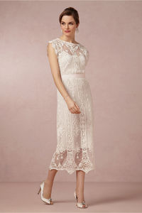 Intricate vintage-inspired lace embroidered onto sheer cotton glides to a romantic scalloped hem while a blush sash cinches the waist on this tea-length dress. From Miguelina. Removable grosgrain sash. Pullover styling. Cotton lace; cotton lining. Dry cle...