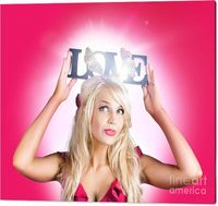 Love Nest Canvas Art | Gorgeous Young Blond Woman Holding Love Sign With Two Butterflies Nesting Together Amongst Bright Rays Of Light On Pink Studio Background | #lovenest #romantic #decor #loveart #bedroomdecor #canvasprints #pinkroom #pinkwallart