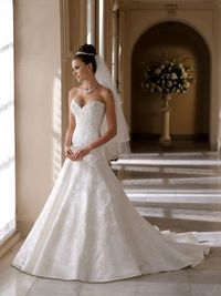 Strapless satin and lace A-line gown, sweetheart neckline with scallop edging, corded lace appliqué bodice with accents of hand-bead Swarvoski crystals and softly curved back bodice, matching beaded lace appliquéd skirt trailing into chapel length train...