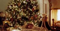 Precious little girl sleeping by the Christmas tree with her dolly tucked in tight. Beautiful Christmas tree and lights.