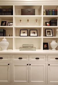 Beautiful built-in vignette with creamy white built-in cabinets & shelves, white carthage pierced lantern, glass boxes, glass & brass decorative boxes and wood jewelry box.