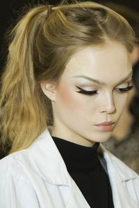 Winged eyeliner and blush high up on the cheeks.