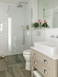 Fantastic bathroom features a gray washstand painted Farrow & Ball Elephant's Breath accented with nickel cup pulls topped with a rectangular vessel sink tucked under a vintage style wall-mount faucet lining a white beveled subway tile backsplash.