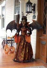 Life-size witch with orange spider web gown and an amazing wing span! A pet spider resides on her head